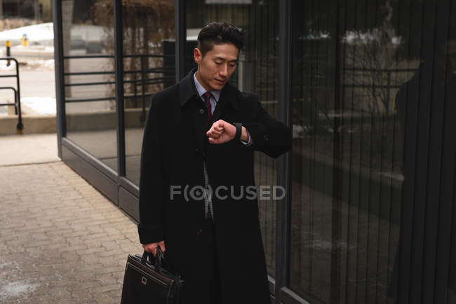 Front view of young well dressed Asian businessman looking at his smartwatch while walking on street in the city — Stock Photo