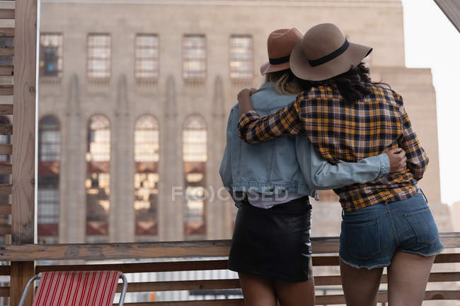Rear view of multi ethnic female friends standing with arm around in balcony at home — Stock Photo