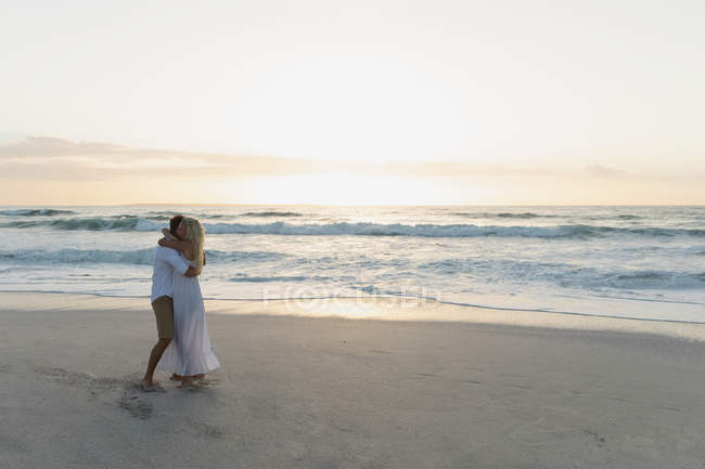 Side view of young love couple hugging each other while standing at beach. They are enjoying their holidays — Stock Photo