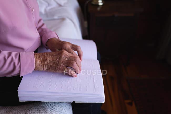 Середине разделе слепая активные старший чтение книги Брайля с ее пальцы сидя на ее кровати в спальне дома — стоковое фото