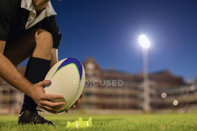 Низький кут зору регбіст розміщення Регбійним м'ячем на здоровий tee на стадіоні вночі — стокове фото