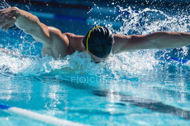 Vorderansicht eines männlichen Schwimmer schwimmen Freestyle Schmetterlings im Schwimmbad an einem sonnigen Tag — Stockfoto