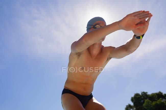 Low angle view of young Caucasian male swimmer in starting position at outdoor swimming pool on sunny day — Stock Photo