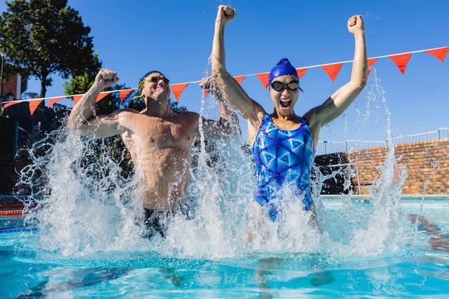 Vista frontal de nadadores masculinos e femininos animados comemorando sua vitória na piscina em um dia ensolarado — Fotografia de Stock