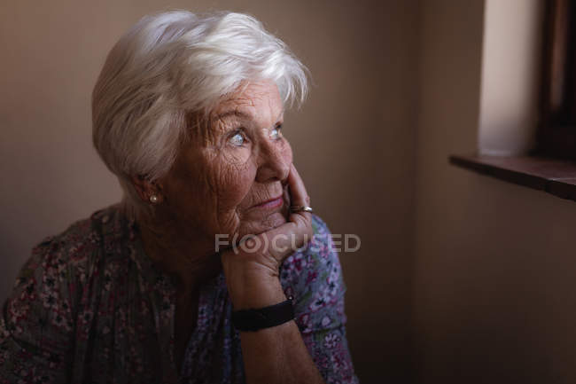 Front view of a thoughtful active senior woman looking through window with her chin leaning on her hand in kitchen at home — Stock Photo