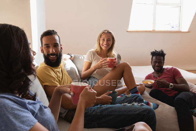Front view of group of diverse people sitting and talking with each other at home — Stock Photo