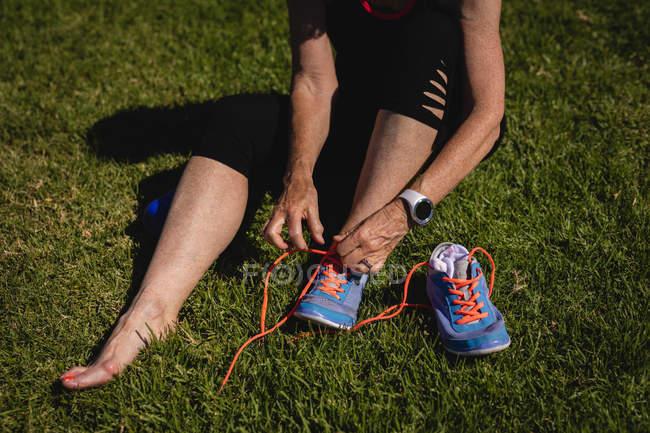 Section basse d'une femme âgée active attachant ses lacets dans le parc par une journée ensoleillée — Photo de stock