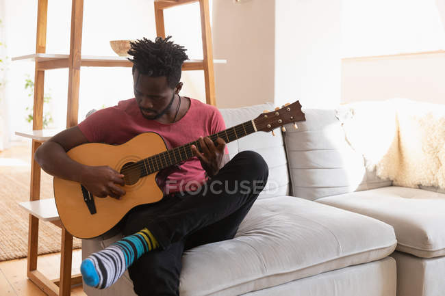 Front view of African american man playing guitar while sitting at home in a living room — Stock Photo