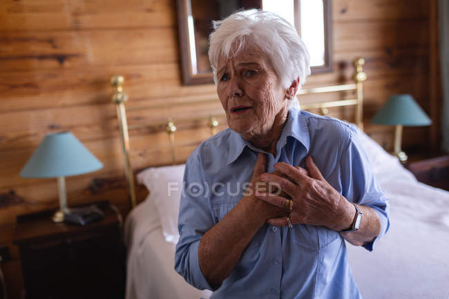 Front view of an active senior woman suffering from chest pain in bedroom at home — Stock Photo