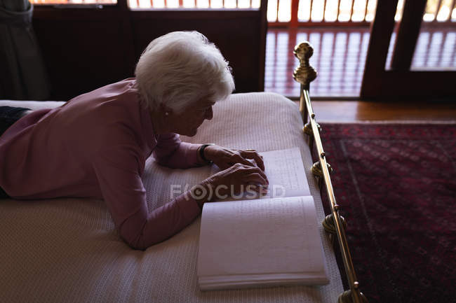 High angle view of a blind active senior woman lying on bed and reading a braille book with her fingers in bedroom at home — Stock Photo
