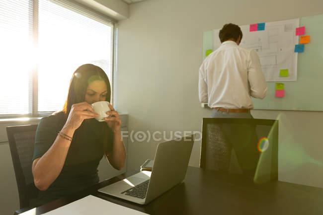 Вид спереди на молодую представительницу смешанной расы с ноутбуком, пьющую вкусный кофе, в то время как коллега-мужчина работает на заднем плане в офисе — стоковое фото