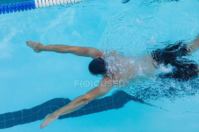 High angle view of a male swimmer swimming breaststroke underwater in the swimming pool — Stock Photo