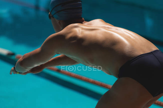 Close-up of young Caucasian male swimmer in starting position at swimming pool on sunny day — Stock Photo