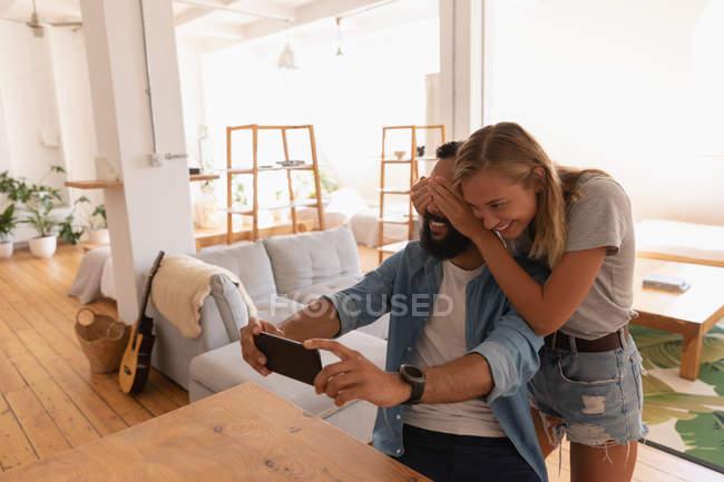 Vue de face de l'homme afro-américain prenant selfie tandis que la femme ferme les yeux à la maison — Photo de stock