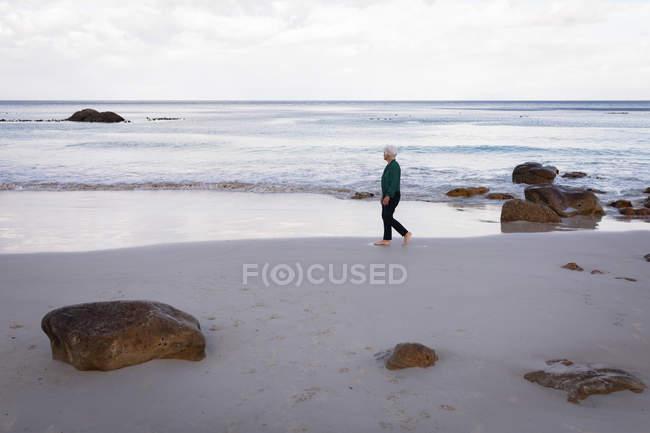 Вид сбоку активного старшие женщины ходить на берегу пляжа — стоковое фото
