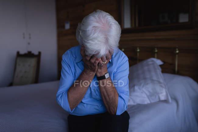 Вид спереди грустной активной пожилой женщины, закрывающей лицо руками, сидя дома на кровати — стоковое фото