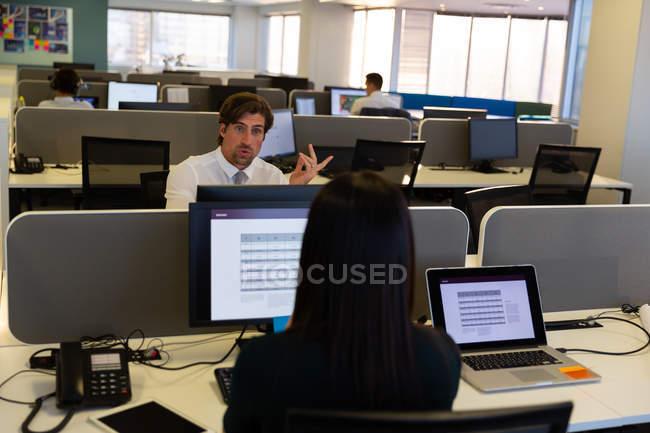 Vista posteriore della dirigente donna che parla con un collega mentre lavora alla scrivania in un ufficio moderno — Foto stock
