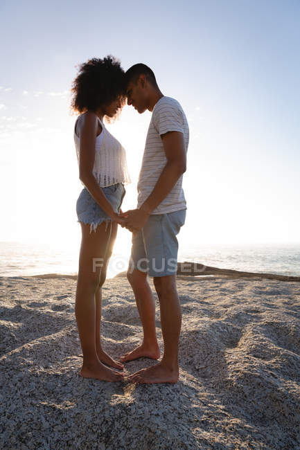 Side view of African-american couple in romantic mood standing on rock near sea side. They are face to face, holding hands and looking each other — Stock Photo