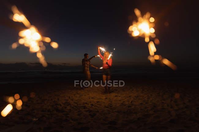 Vista frontale di giovane coppia che gioca con lo sparkler alla spiaggia. Si stanno godendo le loro vacanze — Foto stock