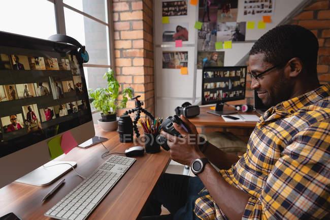 Вид сбоку афро-американского бизнесмена улыбается и смотрит на цифровой фотоаппарат в офисе — стоковое фото