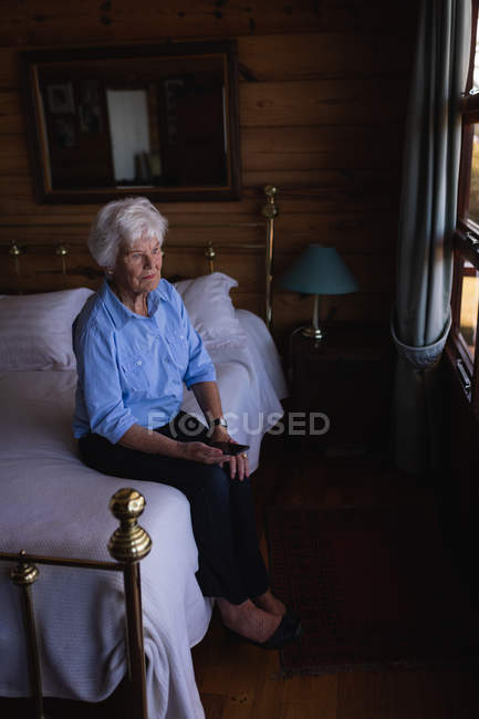 High angle view of a thoughtful active senior woman sitting on the bed and holding her mobile phone in bedroom at home — Stock Photo