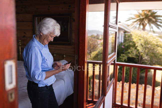Side view of a happy active senior woman using her mobile phone in the bedroom at home — Stock Photo