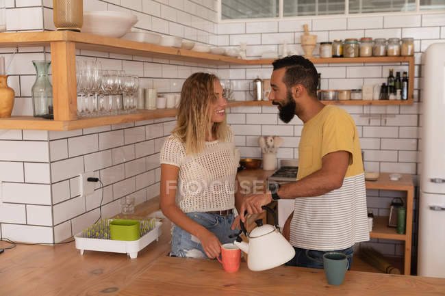 Side view of multi race couple talking with each other at home in kitchen room — Stock Photo