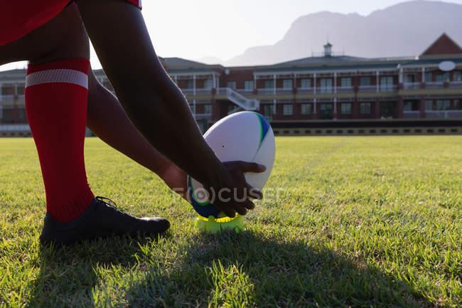 Низкая секция игрока в регби, готовящегося пнуть мяч в регби в солнечный день — стоковое фото