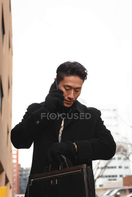 Side view of young Asian businessman looking at smartwatch while talking on mobile phone on street in the city — Stock Photo