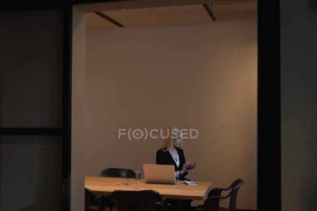 Vorderansicht einer kaukasischen Geschäftsfrau, die ihr Smartphone benutzt, während sie im Büro im Konferenzraum sitzt — Stockfoto