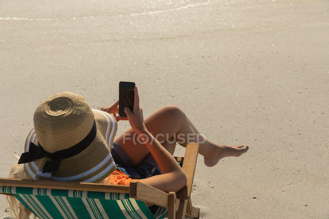 High angle view of young woman relaxing on sun lounger at beach on a sunny day. She is sitting and using her mobile phone — Stock Photo