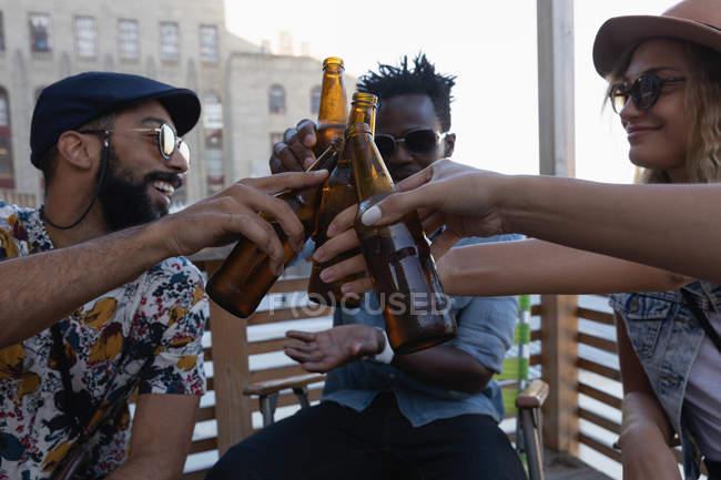 Vista frontal do grupo de amigos diversos brindar com garrafas de cerveja em casa na varanda — Fotografia de Stock