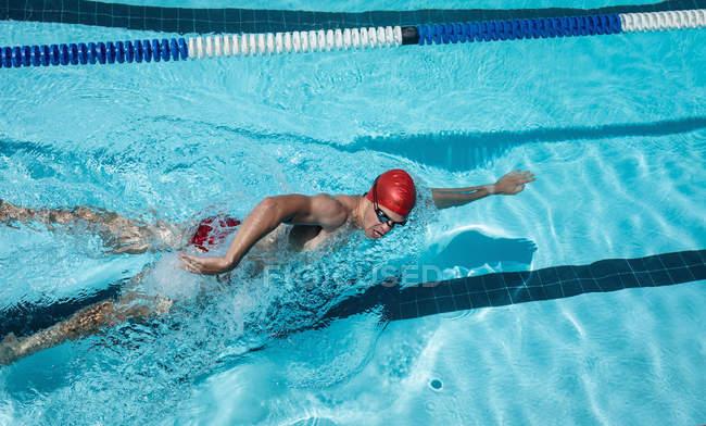Высокий угол обзора молодого кавказского пловца, плавающего вольным стилем в открытом бассейне на солнце — стоковое фото