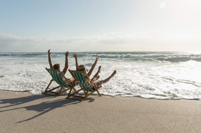 Rear view of young couple enjoying on sun lounger at beach on a sunny day. They are enjoying their holidays - foto de stock
