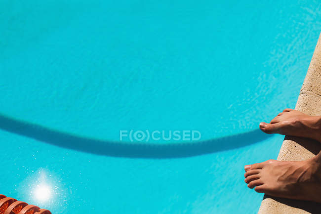 Закри вид босоніж чоловічого плавець стоячи на відкритий плавальний басейн на сонячний день — стокове фото