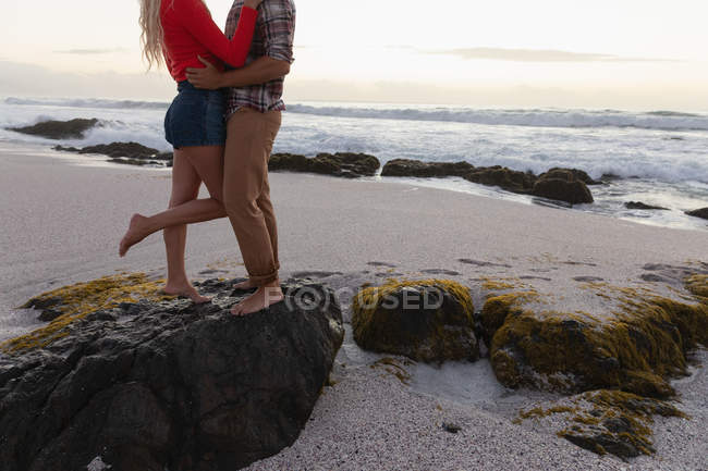 Low section of young couple standing in romantic mood at beach. They hug each other — Stock Photo