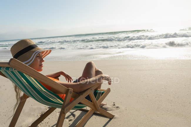 Вид збоку розслабленої молоді жінки розслабляючий на шезлонгу на пляжі у сонячний день. Вона шукає ландшафт — стокове фото