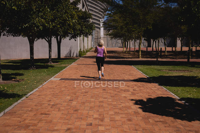 Rear view of an active senior woman doing jogging in the park on a sunny day — Stock Photo