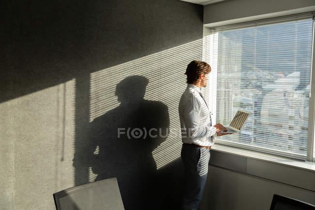 Вид сбоку красивого молодого мужчины с ноутбуком, смотрящего в окно в современном офисе — стоковое фото