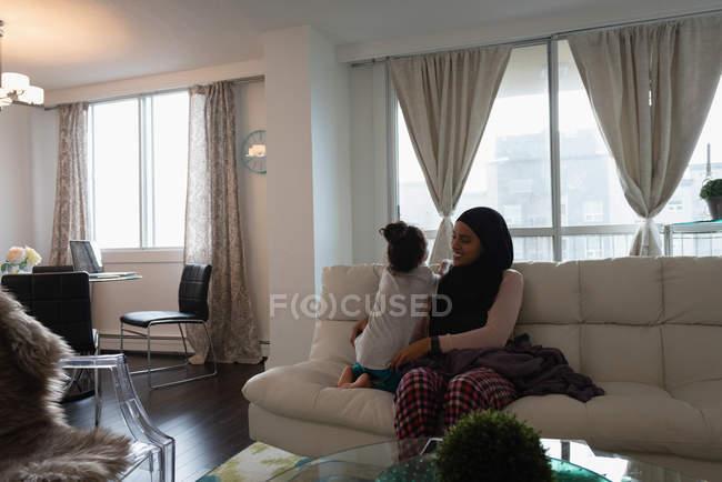 Vista frontale della madre che indossa hijab e figlia che parlano e giocano insieme in salotto a casa — Foto stock