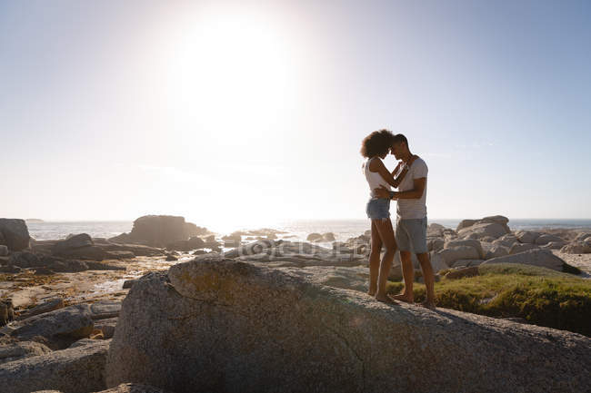 Side view of African-american couple in romantic mood standing on rock near sea side. They are face to face and looking at each others — Stock Photo