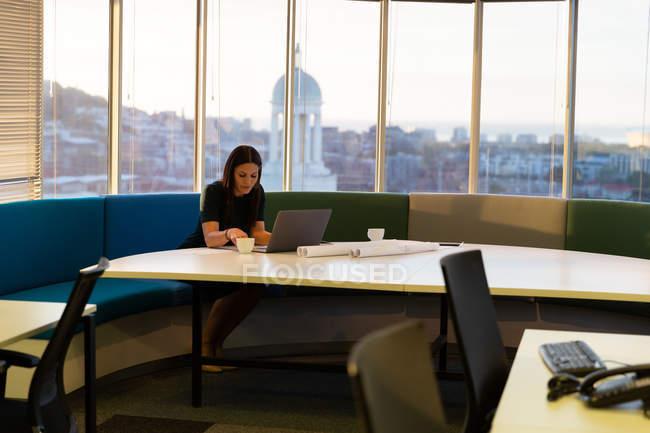 Vista frontale della giovane dirigente donna che lavora sul computer portatile mentre beve una tazza di caffè in un ufficio moderno — Foto stock