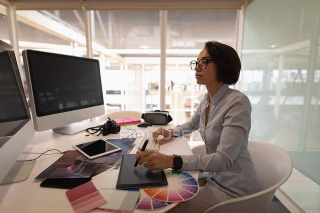 Vista laterale di un designer grafico femminile asiatico lavorando sopra una tavoletta grafica allo scrittorio in ufficio — Foto stock