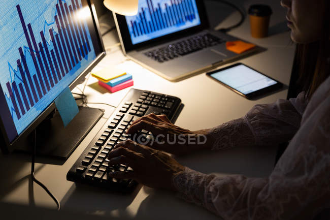 Mid section of young female executive working on computer at desk in a modern office. She is working late — Stock Photo