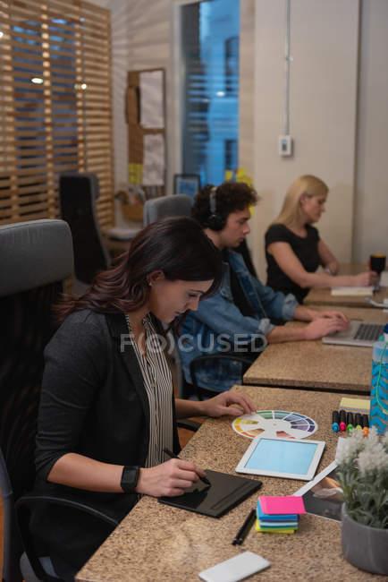 Vista laterale di donna d'affari ben vestita che utilizza tablet grafico mentre guarda campione di colore con i colleghi che lavorano duramente in ufficio — Foto stock