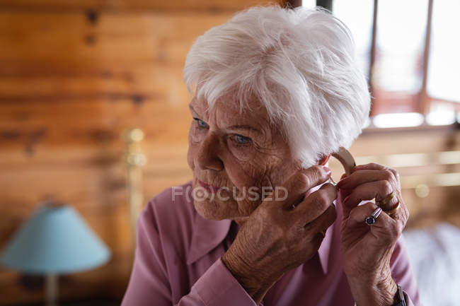 Front view of an active senior woman wearing a hearing aid in her ear in bedroom at home the — Stock Photo
