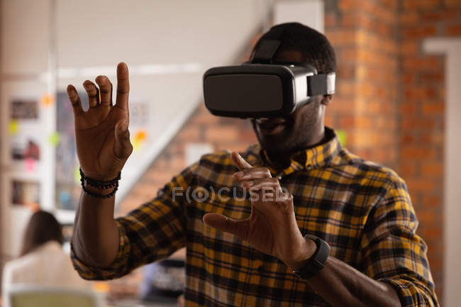 Front view of african american businessman using virtual reality headset in office — Stock Photo