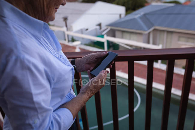 Mid section of an active senior woman using her mobile phone while standing in a balcony at home — Stock Photo