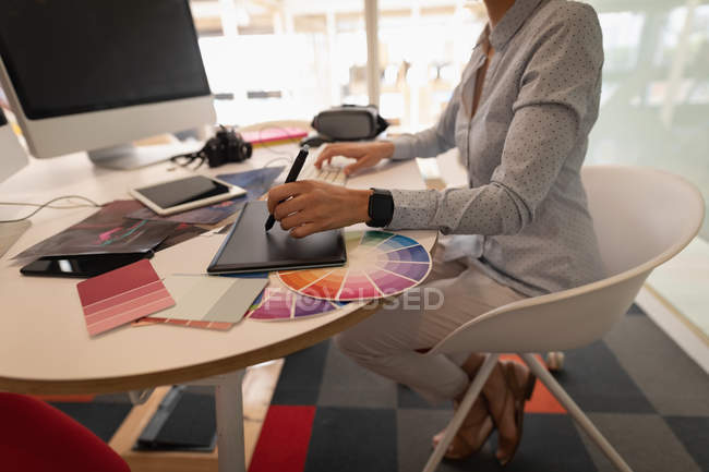 Low section of a female graphic designer working over a graphic tablet at desk in office — Stock Photo