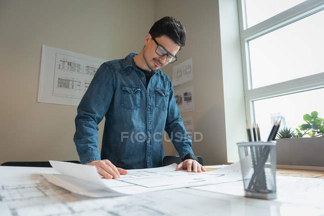 Low angle view of diverse businessman standing and working over blueprint at office conference — Stock Photo